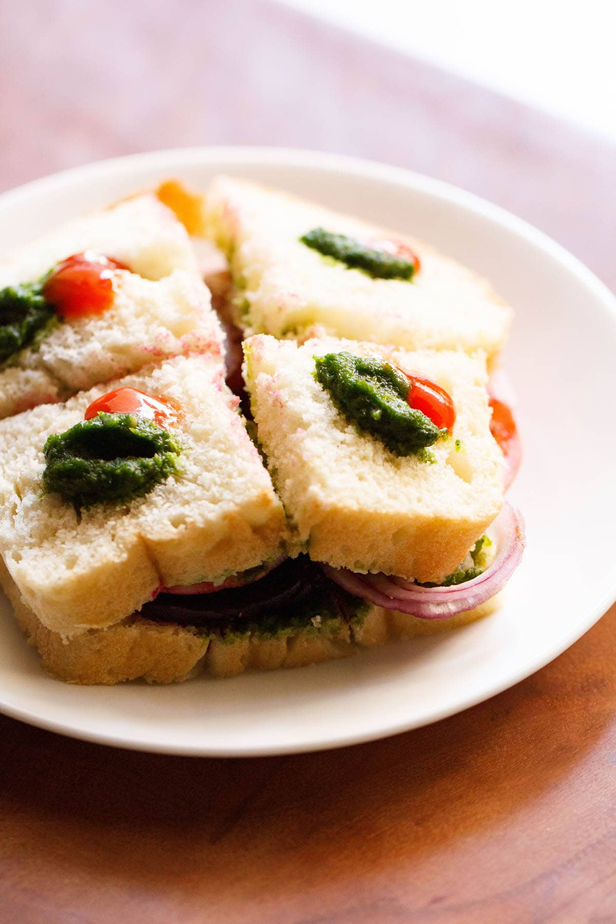bombay sandwich dotted with green sauce and ketchup on a white plate