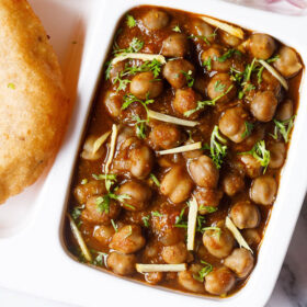 white plate with sections filled with chana masala, sliced onions, fresh lime wedges and bhatura on a marble table-top