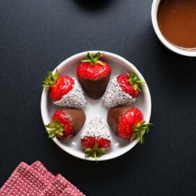 chocolate covered strawberries in a white bowl on black board