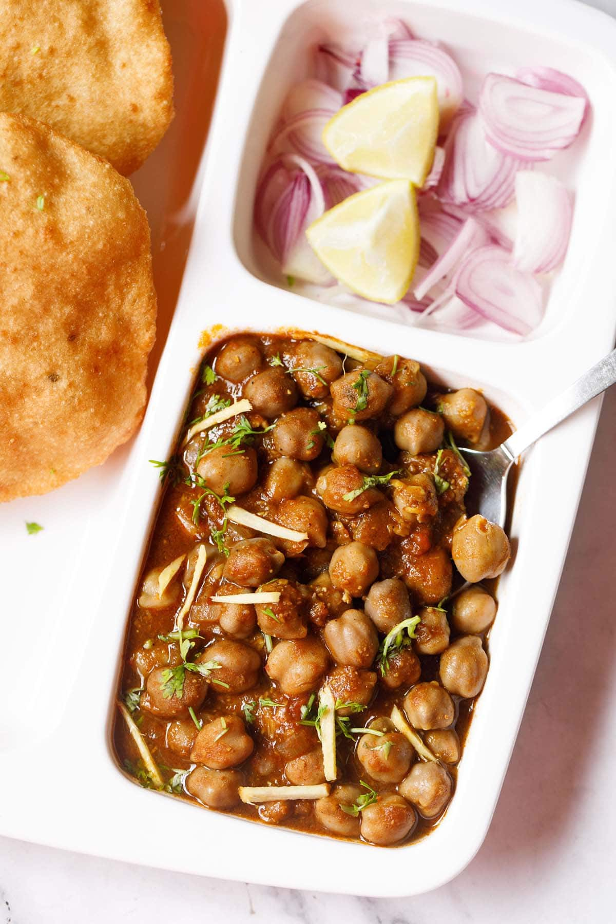 white plate with sections filled with chole masala, sliced onions, fresh lime wedges and bhatura on a marble table-top