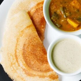two folded, golden, crisp placed next to white bowls filled with sambar and coconut chutney on a white plate