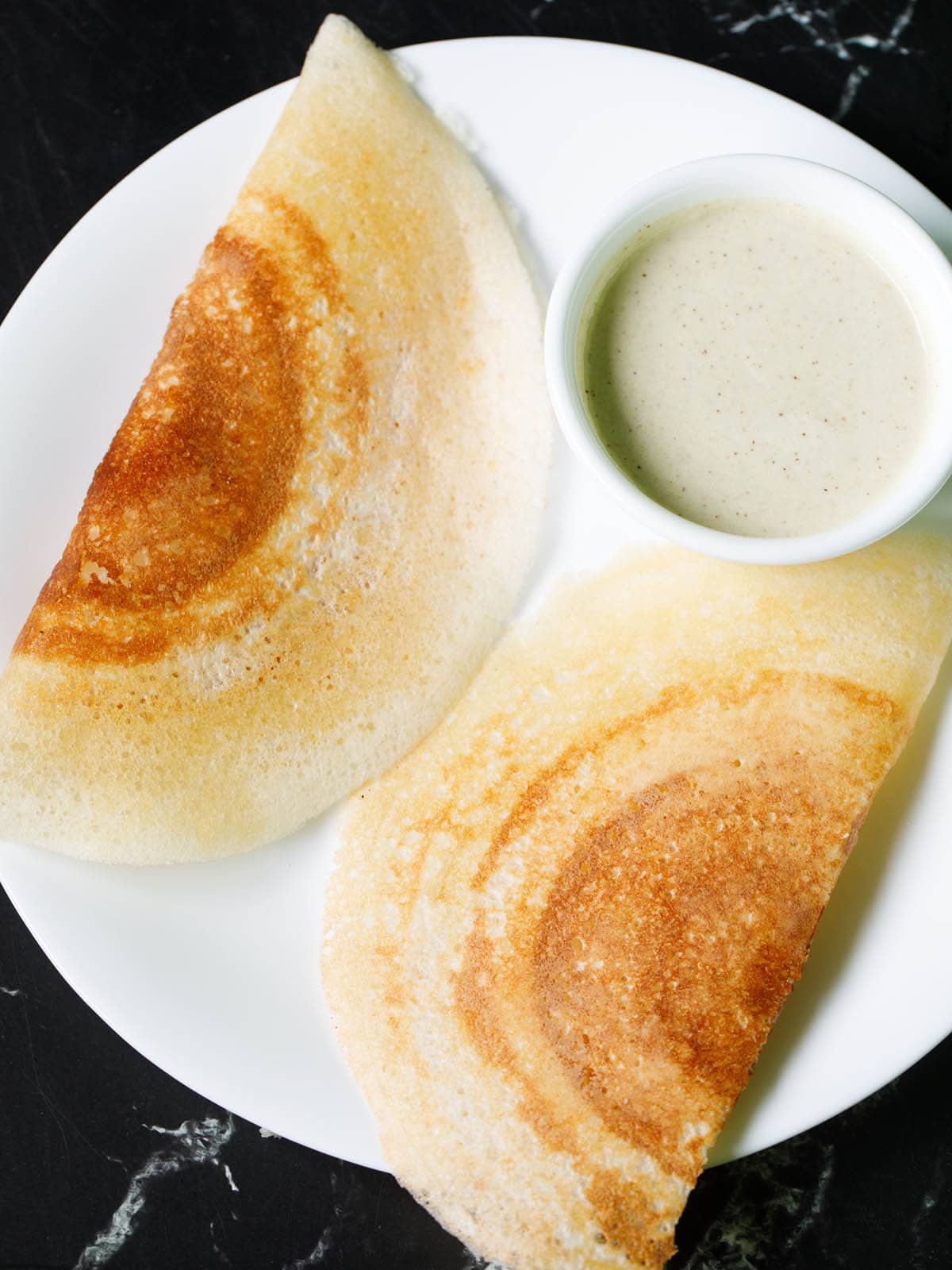two crisp and golden dosa with a bowl of coconut chutney on a white plate