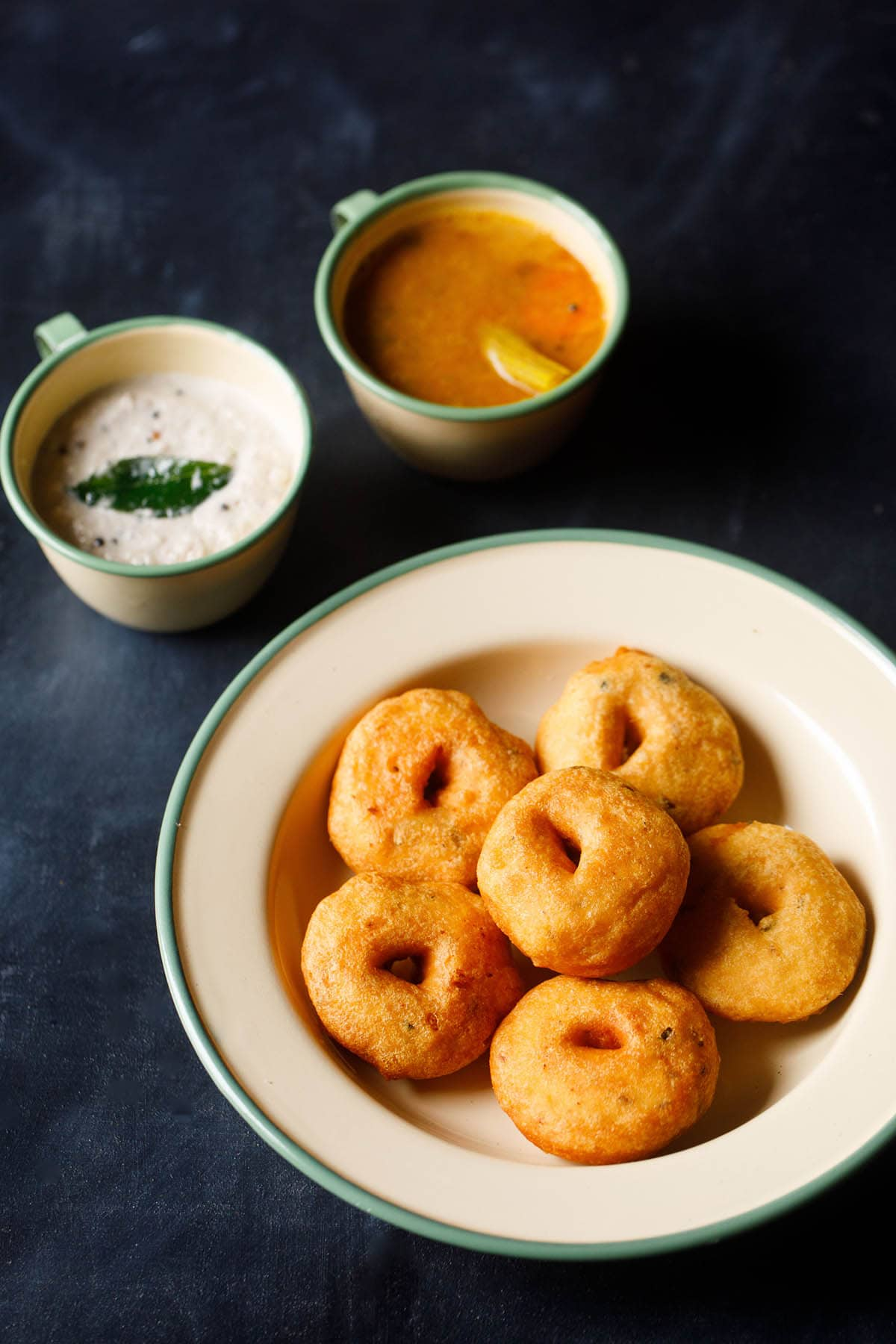 top shot of medu vada stacked neatly in green lined beige colored plate with cups filled with coconut chutney and sambar on the top