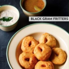 top shot of medu vada stacked neatly in green lined beige colored plate with cups filled with coconut chutney and sambar on the top with text layovers
