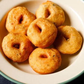 medu vada stacked neatly in green lined beige colored plate