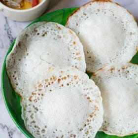 overhead shot of kerala appams on a green plate with vegetable stew in white bowl placed on top