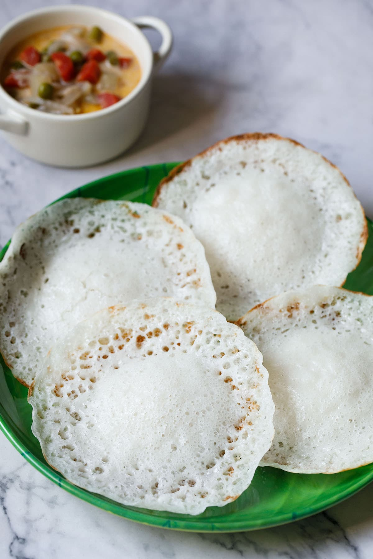 four appam on green plate