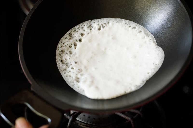 swirling dough around pan to create a round appam