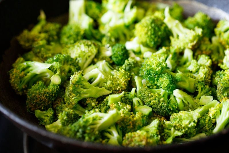 adding broccoli florets to the pan