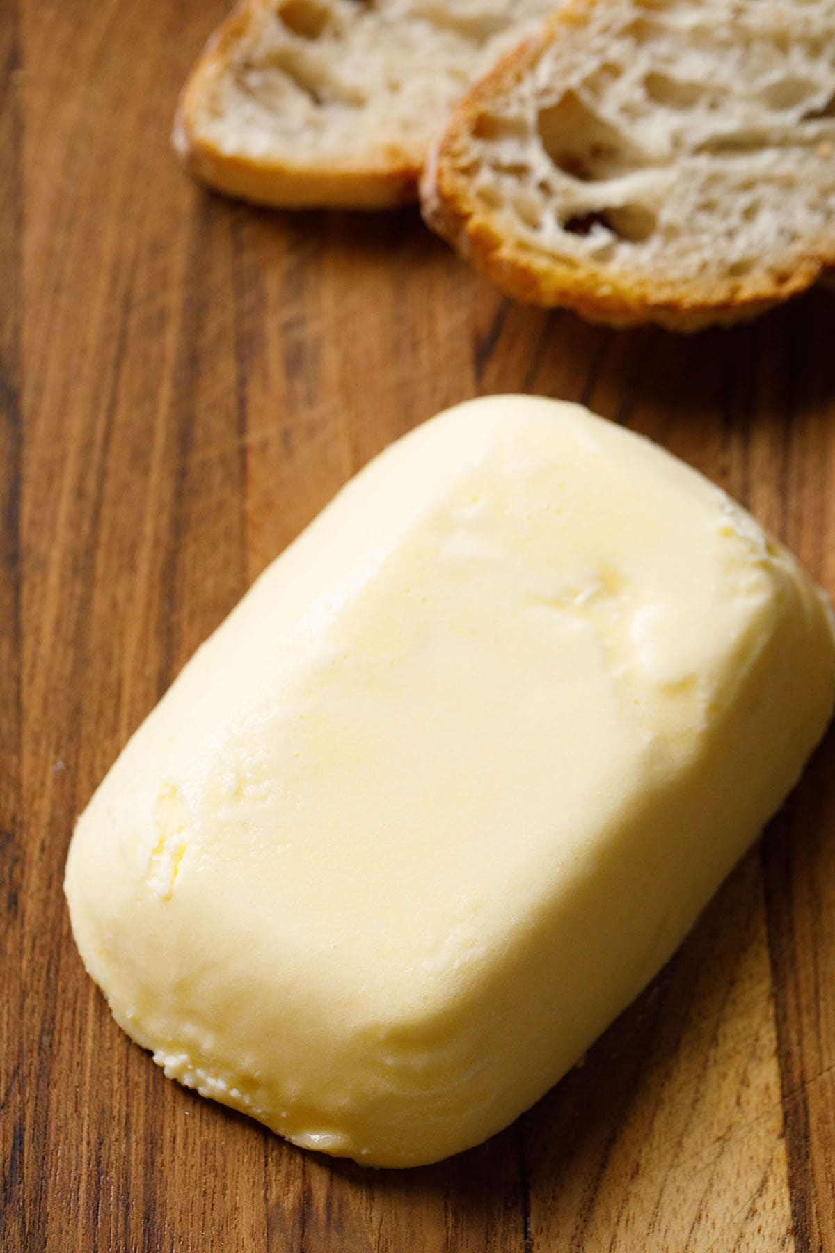 block of homemade butter on brown wooden board with baguette slices on top