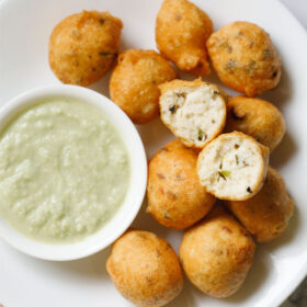 overhead shot of white plate having halved mysore bonda showing the fluffy texture on top of remaining bonda next to a side of light green coconut chutney