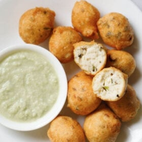 overhead shot of white plate having halved mysore bonda showing the fluffy texture on top of remaining bonda next to a side of light green coconut chutney with text layovers