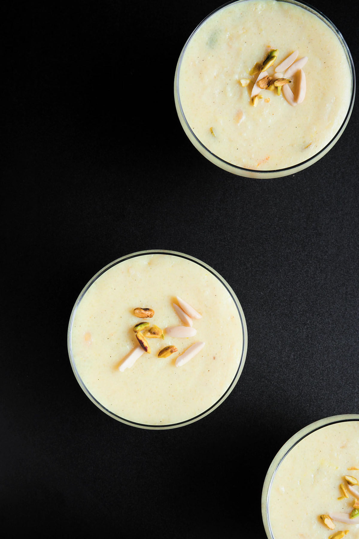 overhead shot of phirni in glass bowls on black board