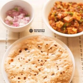 top shot of roti smeared with ghee on a white plate with two white bowls of paneer curry and chopped red onions placed above on a cream cotton fabric with text layovers