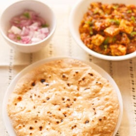 roti smeared with ghee on a white plate with two white bowls of paneer curry and chopped red onions placed above on a cream cotton fabric
