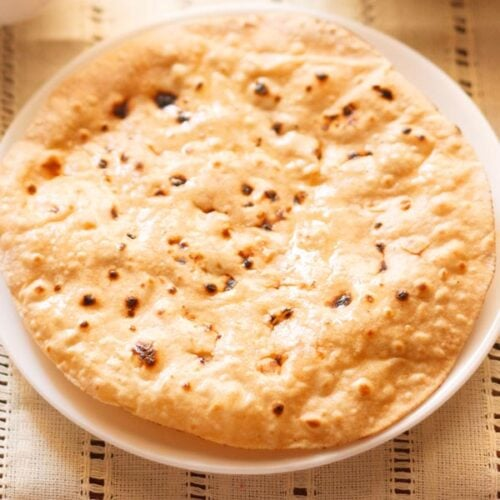 roti or chapati in a white plate on a cream cotton fabric