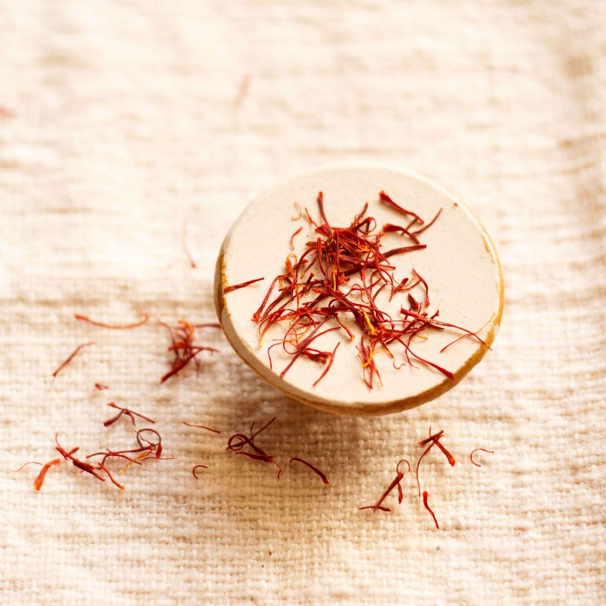saffron strands on a round beige holder on burlap