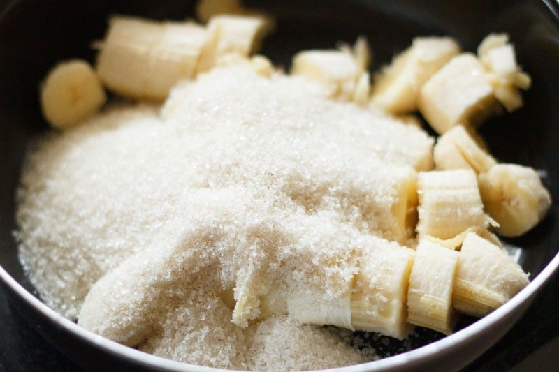 Top shot of sliced bananas with sugar on top in black bowl
