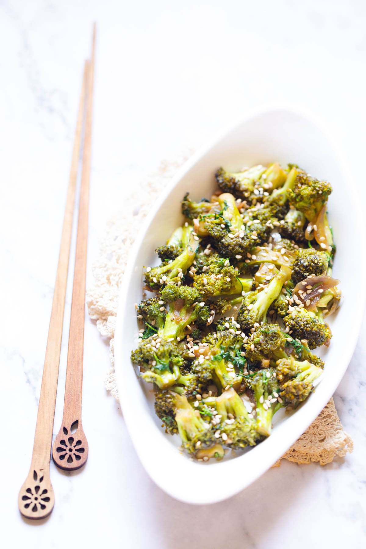 broccoli stir fry in a white oval plate with wooden chopsticks by the side