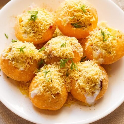 closeup shot of dahi puri sprinkled with sev and coriander leaves in a white plate