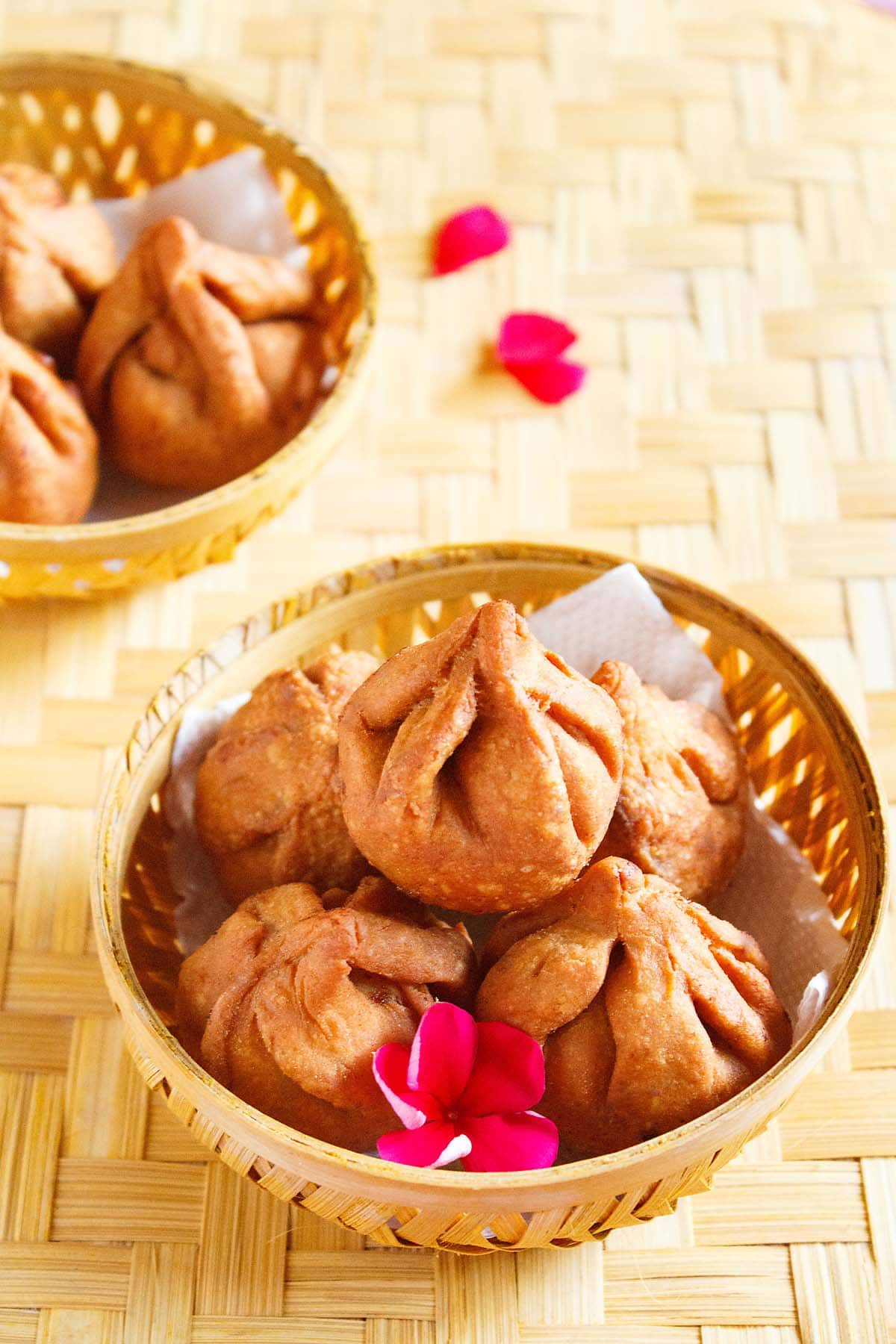 fried modak in a round bamboo bowl with a dark pink flower placed on a bamboo mat