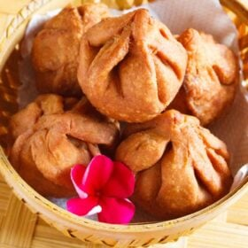 closeup shot of fried modak in a round bamboo bowl with a dark pink flower inside