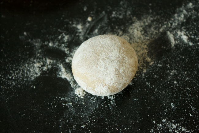 flattened round of dough sprinkled with flour on a flour dusted surface