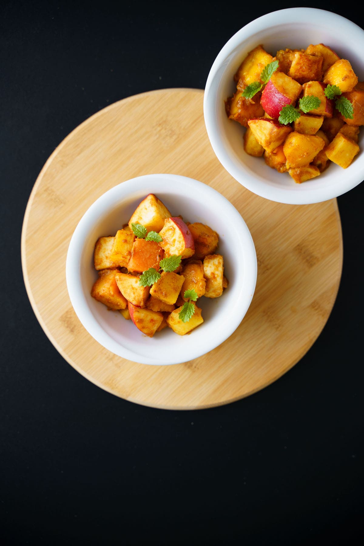 overhead shot of fruit chaat in white bowls on a round bamboo board