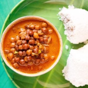 overhead shot of kadala curry in a green bowl on a green plate with two puttu by the side