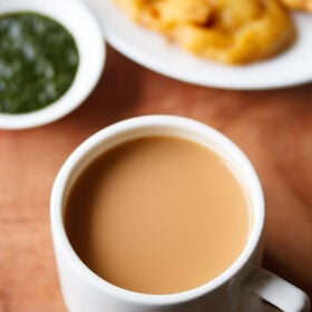 masala chai filled in a white cup with a side of onion pakora in white plate and green chutney in small white bowl