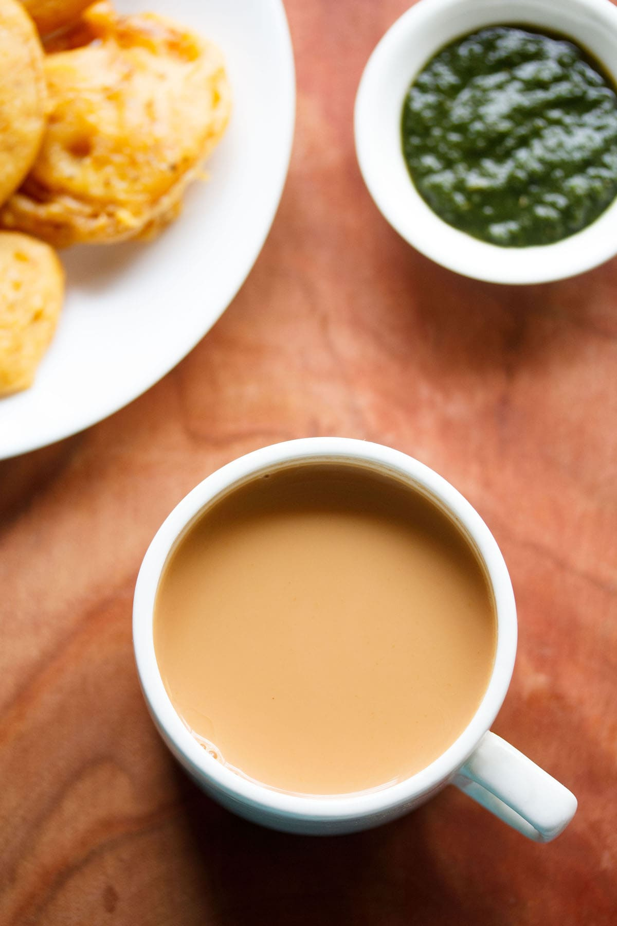 overhead shot of masala teain a white cup on brown board
