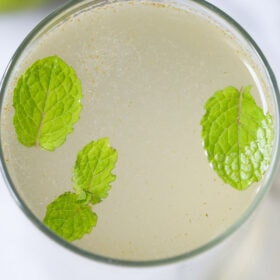 closeup shot of shikanji in a glass with mint leaves