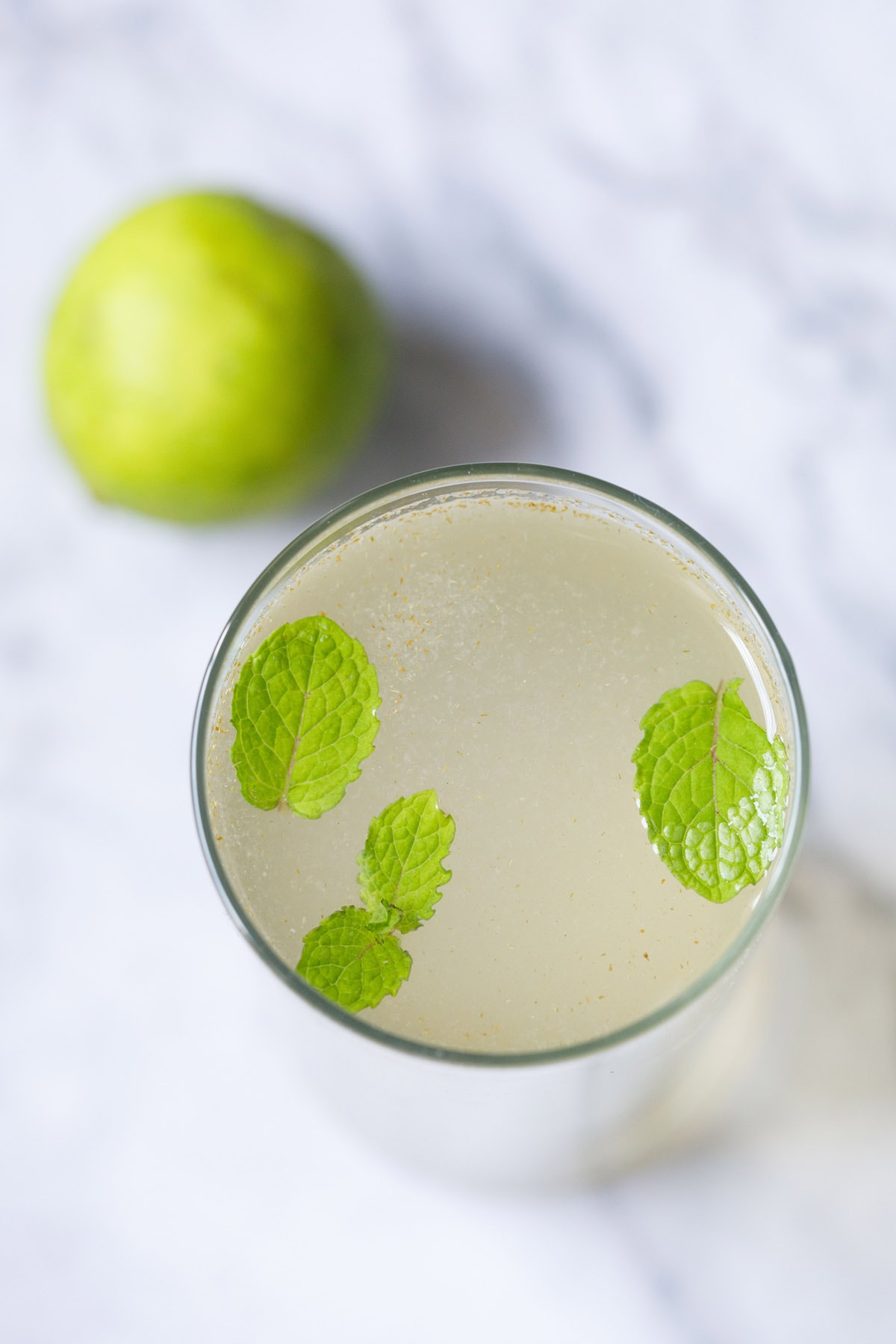 overhead shot of closeup shot of shikanji in a glass with mint leaves with a lemon placed near top left of the glass