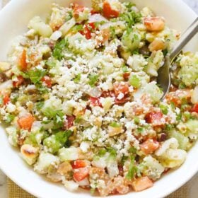 vegetable salad topped with crumbled feta and parsley with a spoon in a white bowl