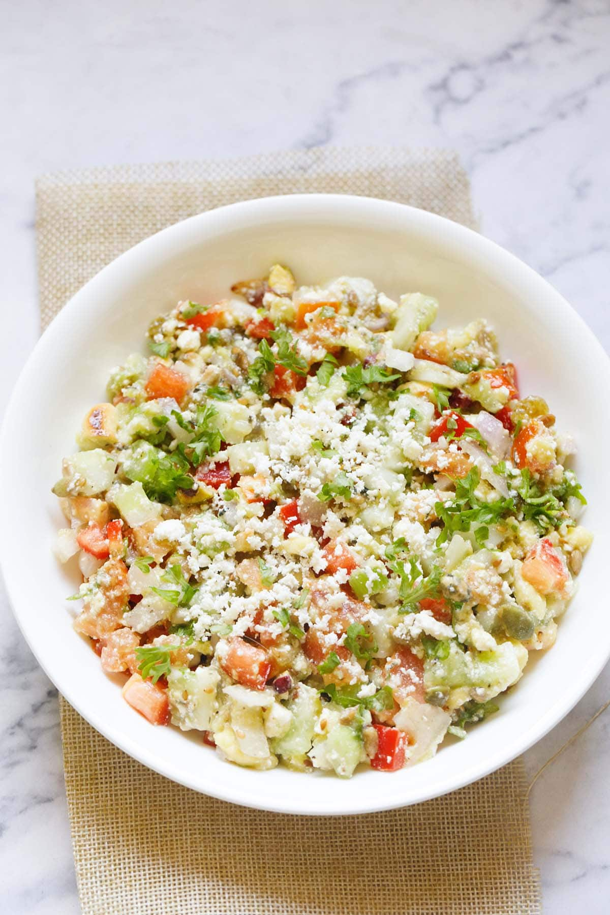 overhead shot of vegetable salad topped with crumbled feta and parsley in a white bowl