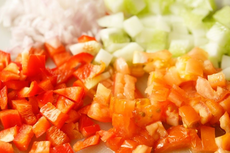 evenly diced onions, cucumbers, tomatoes and bell pepper on a cutting board