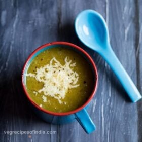 pumpkin soup in blue cup with blue spoon